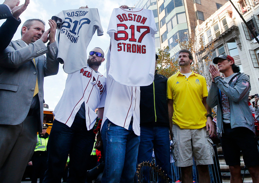 . Boston Red Sox\'s Jonny Gomes, second from left, and Jarrod Saltalamacchia hold up baseball jerseys during a pause in their World Series victory rolling rally in Boston, Saturday, Nov. 2, 2013, to remember those affected by the Marathon bombing. They presented the jerseys to workers at two of the businesses at the bombing sites, including, second from right, Shane O\'Hara and at far right, Dan Solo. (AP Photo/Elise Amendola)