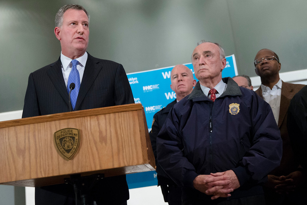 . New York City Mayor Bill de Blasio, left, speaks alongside NYPD Commissioner Bill Bratton, right, stands beside during a news conference at Woodhull Medical Center, Saturday, Dec. 20, 2014, in New York.  An armed man walked up to two New York Police Department officers sitting inside a patrol car and opened fire Saturday afternoon, killing one and critically wounding a second before running into a nearby subway station and committing suicide, police said. (AP Photo/John Minchillo)