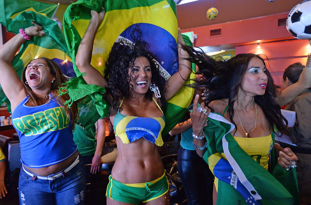 . Brazil soccer fans Jane Guimaraes, left, Marisa Cortez, center, and Joany Macias, right, cheer as Brazil scores against Croatia. Fans crowded into Samba restaurant to watch the FIFA World Cup game against Croatia Thursday, June 12, 2014, Redondo Beach, CA.  The South Bay is home to a large Brazilian community. Photo by Steve McCrank/Daily Breeze