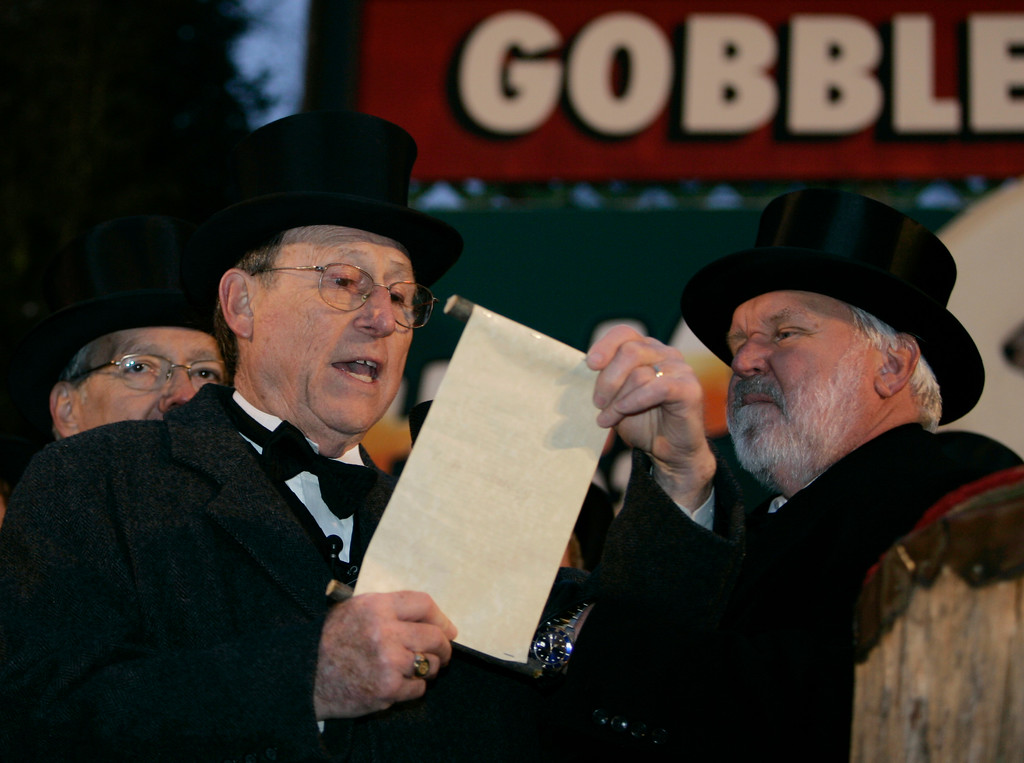 . Rusty Johnston, left, reads Punxsutawney Phil\'s prediction of an early spring in Punxsutawney, Pa., Friday, Feb. 2, 2007. Standing next to Johnston is Mike Johnston.  Phil, the weather predicting groundhog, did not see his shadow on Friday which, according to German folklore, means folks can expect an early spring instead of six more weeks of winter.     (AP Photo/Carolyn Kaster)