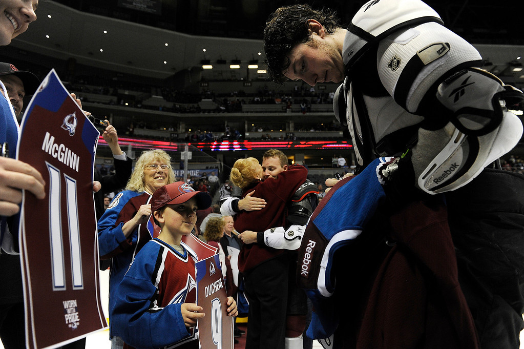 . Matt Duchene (9) of the Colorado Avalanche signs his jersey before handing it off to Nathan Truax, 8, of Littleton during the Sweaters Off Our Backs promotion following the third period on Saturday, April 27, 2012 at Pepsi Center. Seth A. McConnell, The Denver Post