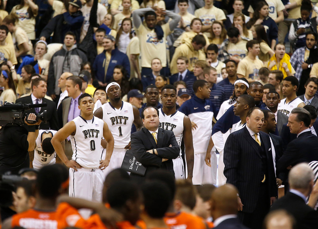 . Pittsburgh\'s James Robinson (0), Jamel Artis (1), Michael Young, center right, look on with director of men\'s basketball operations Brian Regan, center, as the officials check the replay on the time of the last shot of the second half of an NCAA college basketball game against Syracuse on Wednesday, Feb. 12, 2014, in Pittsburgh. Syracuse won 58-56 on the three point shot with less than a second left in the game. (AP Photo/Keith Srakocic)