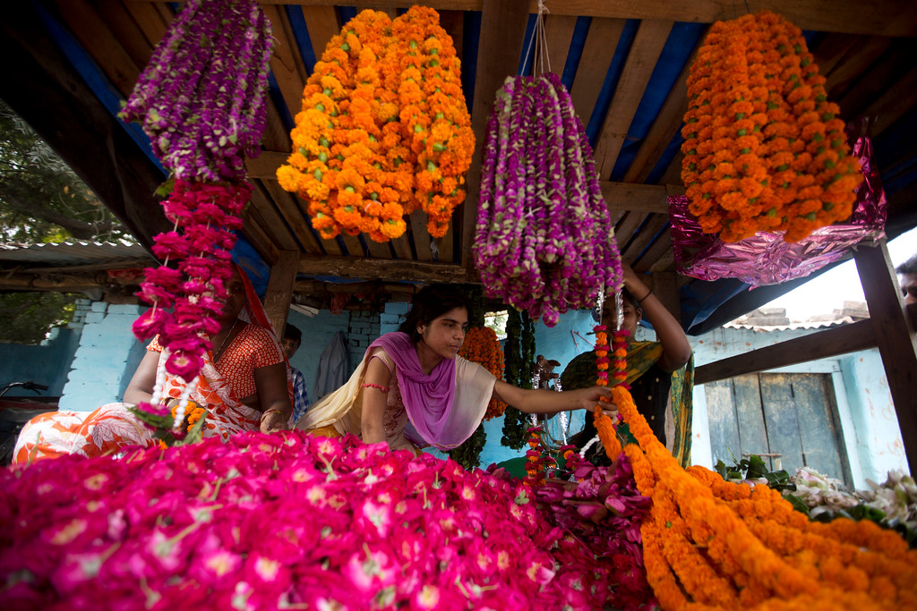 . Vendors sell marigold flower garlands, commonly used to decorate homes and perform rituals, during Diwali festival in Allahabad, India, Thursday, Oct. 19, 2017. Hindus light lamps, wear new clothes, exchange sweets and gifts and pray to goddess Lakshmi during Diwali, the festival of lights. (AP Photo/Rajesh Kumar Singh)