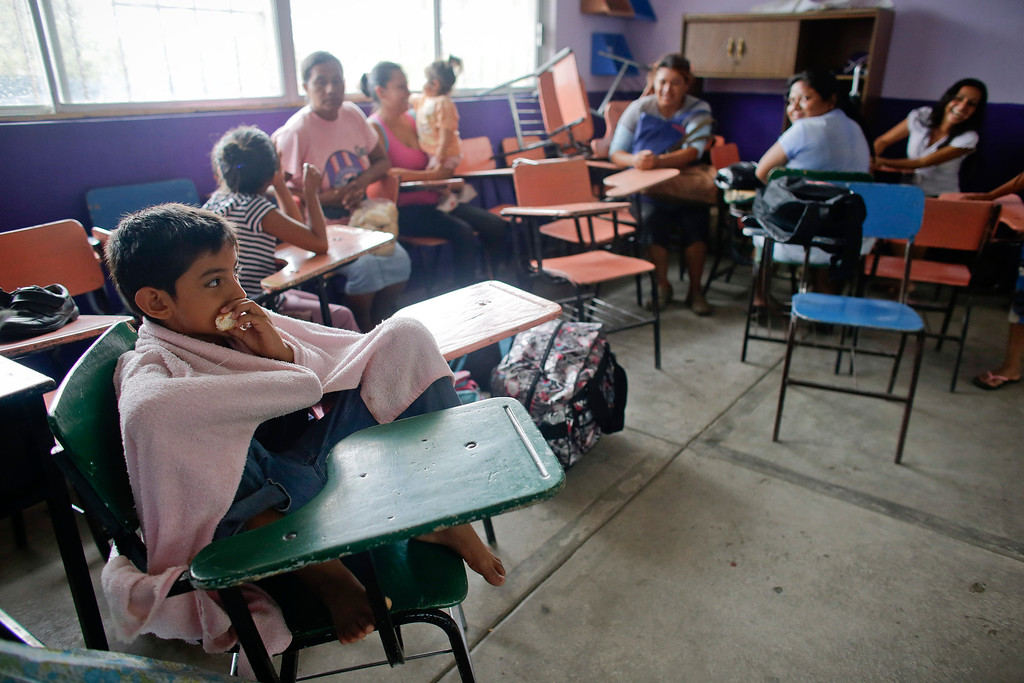 . A child eats a piece of bread as families rest in school-turned shelter after being evacuated from their homes in Los Cabos, Mexico,  Sunday, Sept. 14, 2014. Hurricane Odile is expected to make a close brush with the southern portion of Mexico\'s Baja California peninsula Sunday evening. (AP Photo/Victor R. Caivano)