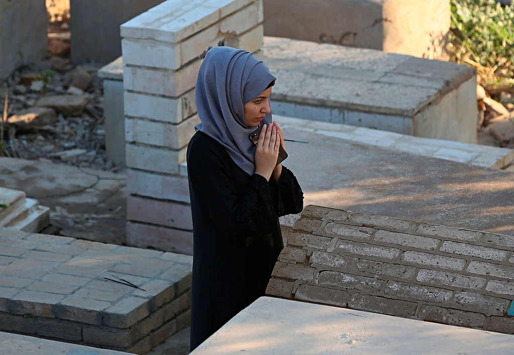 . A woman prays near the grave of her relative during the first day of Eid al-Fitr in Ghazali cemetery, Baghdad, Iraq, Friday, June 15, 2018. Eid al-Fitr marks the end of the Muslims\' holy month of Ramadan. (AP Photo/Hadi Mizban)