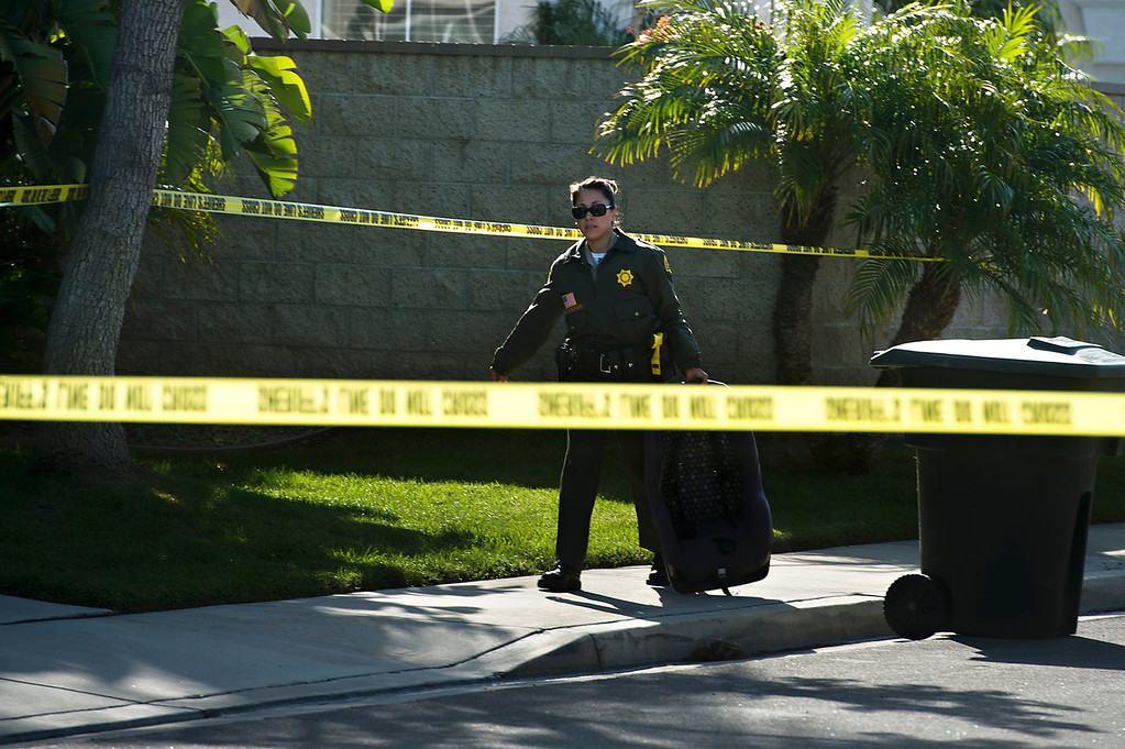 . A San Bernardino County sheriff\'s deputy walks exits the crime scene carrying a baby car seat after a fatal deputy-involved shooting in 5400 block of Brushwood Court in Chino Hills on Friday, March 28, 2014. f(Photo by Watchara Phomicinda/ San Gabriel Valley Tribune)