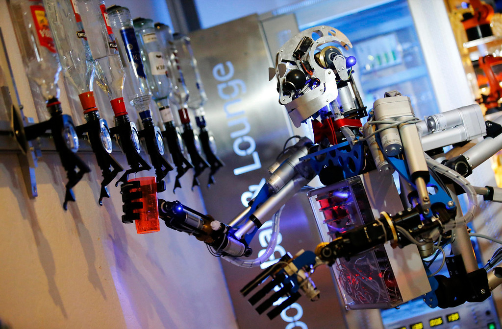 ". Humanoid robot bartender ""Carl\"" fills a cocktail glass with spirits to prepare a drink for a guest at the Robots Bar and Lounge in the eastern German town of Ilmenau, July 26, 2013. \""Carl\"", developed and built by mechatronics engineer Ben Schaefer who runs a company for humanoid robots, prepares spirits for the mixing of cocktails and is able to interact with customers in small conversations. Picture taken July 26, 2013. REUTERS/Fabrizio Bensch"