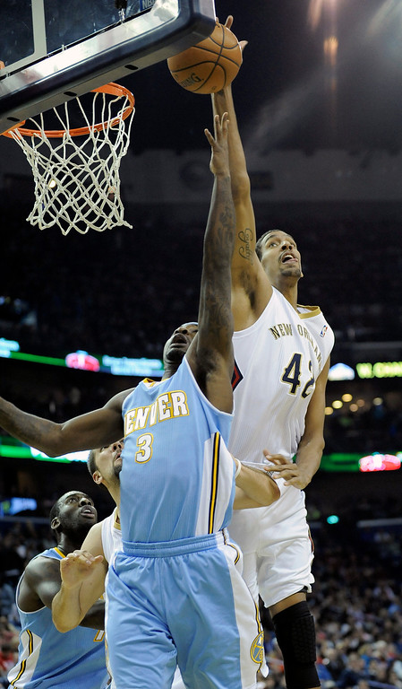 . New Orleans Pelicans center Alexis Ajinca (42) blocks a shot by Denver Nuggets guard Ty Lawson (3) in the first half of an NBA basketball game in New Orleans, Friday, Dec. 27, 2013.  (AP Photo/Stacy Revere)