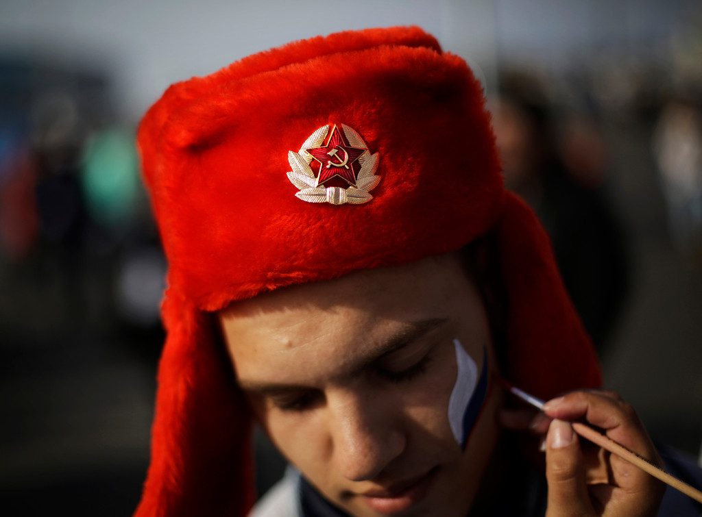 . An emblem with the Soviet hammer and sickle decorates the hat of Serdar Yuldashev as he has his face painted in the colors of the Russian flag at the Olympic Park at the 2014 Winter Olympics, Thursday, Feb. 20, 2014, in Sochi, Russia. (AP Photo/David Goldman)