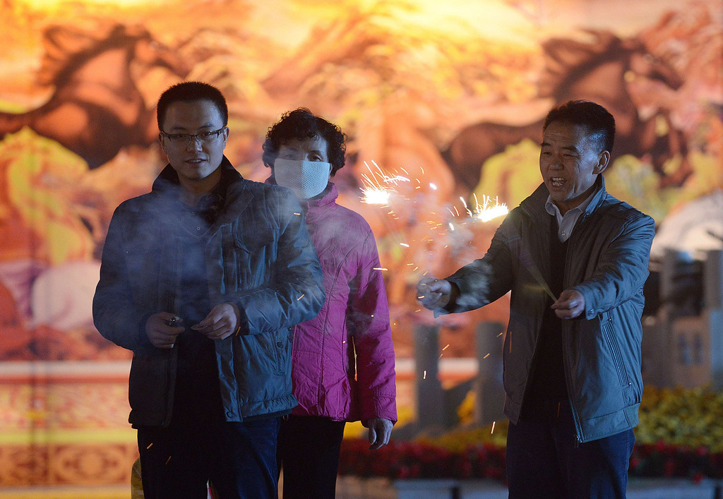 . A Chinese family lights fireworks at a square in Lanzhou, northwest China\'s Gansu province, on January 30, 2014, on the eve of the Lunar New Year.  AFP PHOTO / WANG ZHAO/AFP/Getty Images