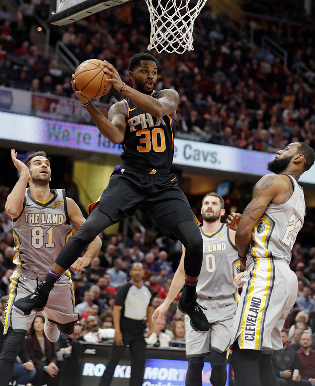 . Phoenix Suns\' Troy Daniels (30) looks to pass against Cleveland Cavaliers\' Jose Calderon (81), from Spain, and LeBron James (23) during the first half of an NBA basketball game Friday, March 23, 2018, in Cleveland. (AP Photo/Tony Dejak)