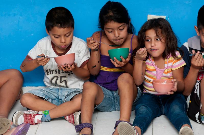 Children enjoy snack of rice porridge.