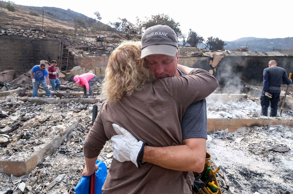 . Craig Bolleson hugs his friend in his burned out home, Monday, Sept. 4, 2017, in the Sunland-Tujunga section of Los Angeles. Wildfires forced thousands to flee their homes across the U.S. West during a sweltering, smoke-shrouded holiday weekend of record heat. (AP Photo/Ringo H.W. Chiu)
