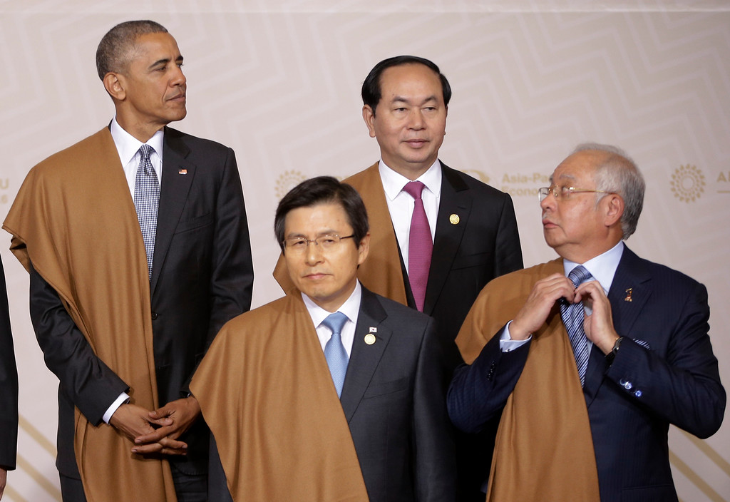 ". Malaysia\'s Prime Minister Najib Razak arranges his tie as he waits with U.S. President Barack Obama, top left, South Korea\'s Prime Minister Hwang Kyo-ahn, front left, and Vietnam\'s President Tran Dai Quang for the group photo at the annual Asia Pacific Economic Cooperation, APEC, summit in Lima, Peru, Sunday, Nov. 20, 2016.  The APEC forum closed with a joint pledge to work toward a sweeping new free trade agreement that would include all 21 members as a path ""sustainable, balanced and inclusive growth,\"" despite the political climate. (AP Photo/Martin Mejia)"