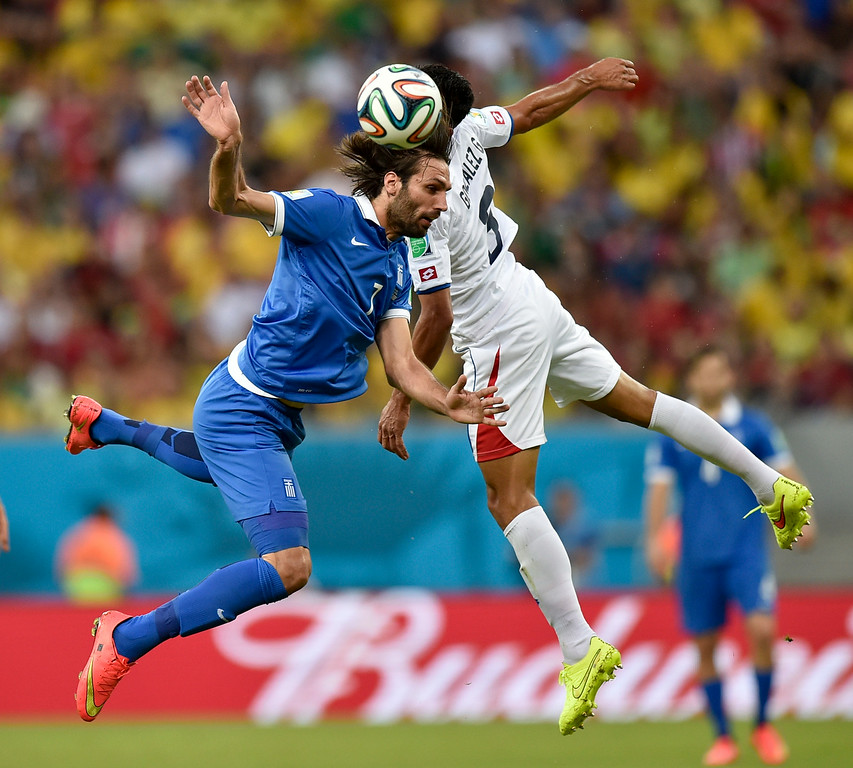 . Greece\'s Giorgos Samaras, left, and Costa Rica\'s Michael Umana go up against one another to head the ball during the World Cup round of 16 soccer match between Costa Rica and Greece at the Arena Pernambuco in Recife, Brazil, Sunday, June 29, 2014. (AP Photo/Martin Meissner)