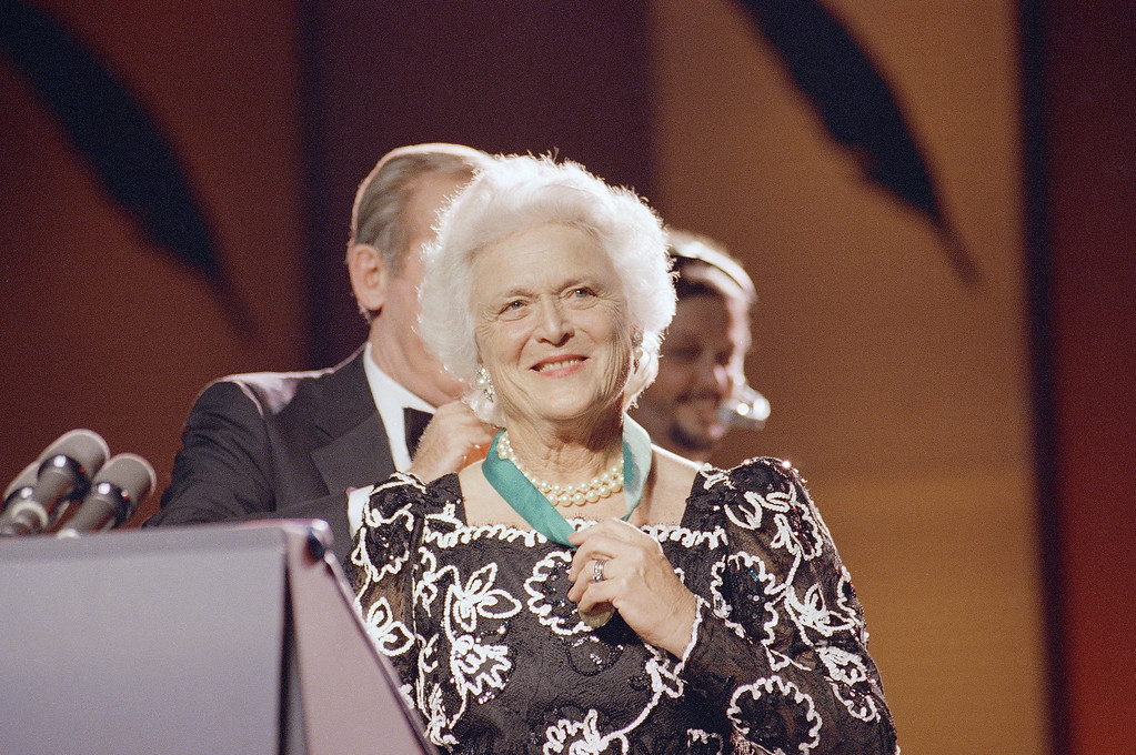 . Barbara Bush, wife of President-Elect George Bush, smiles as James Duffy, President of ABC-Capital Cities, places a medal around her neck during the National Literary Honors Dinner, Tuesday, Nov. 15, 1988 in Washington. The future first lady was honored for her literacy efforts. (AP Photo/J.Scott Applewhite)