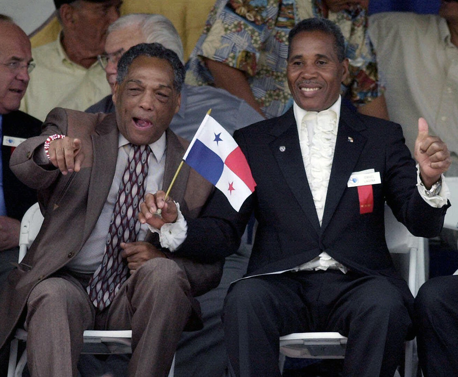 . FILE - In this June 10, 2001, file photo, International Boxing Hall of Fame inductees Sugar Ramos of Mexico, front left, and Ismael Laguna of Panama, gesture during induction ceremonies in Canastota, N.Y. Ramos, the Cuban featherweight champion whose fists led to two deaths in the ring, has died in Mexico City. He was 75. The World Boxing Council said he died Sunday, Sept. 3, 2017, of cancer. (AP Photo/Kevin Rivoli, File)