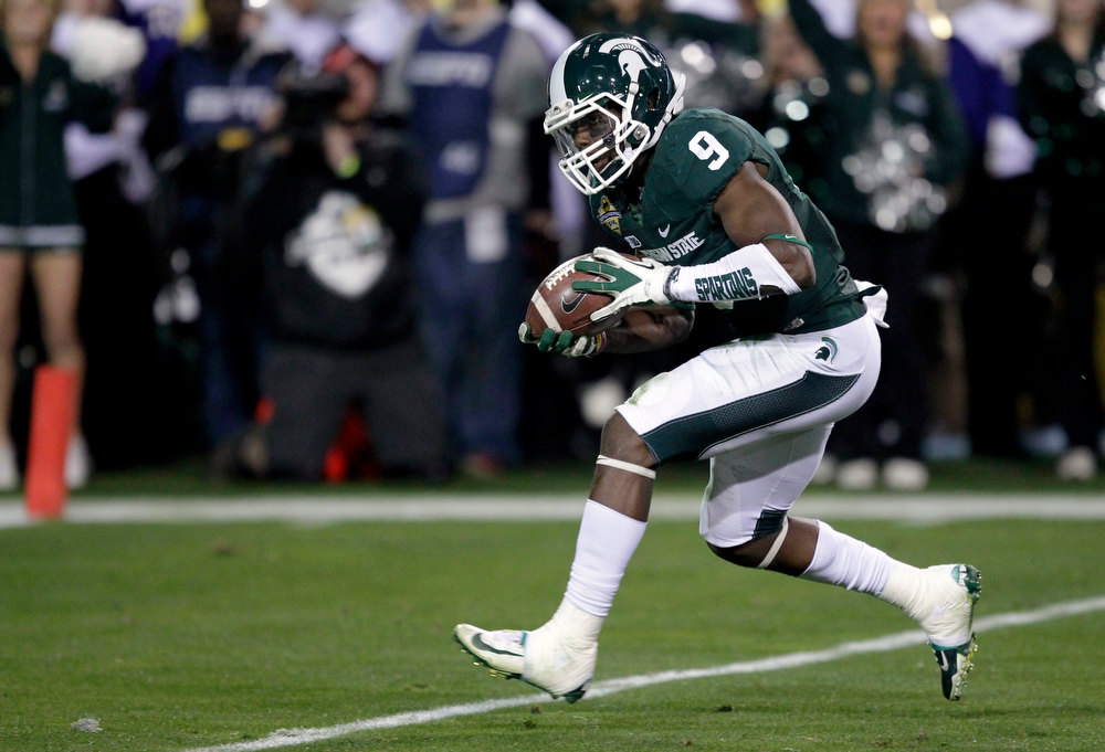 Description of . Michigan State safety Isaiah Lewis (9) intercepts a pass against TCU during the first half of the Buffalo Wild Wings Bowl NCAA college football game, Saturday, Dec. 29, 2012, in Tempe, Ariz. (AP Photo/Matt York)
