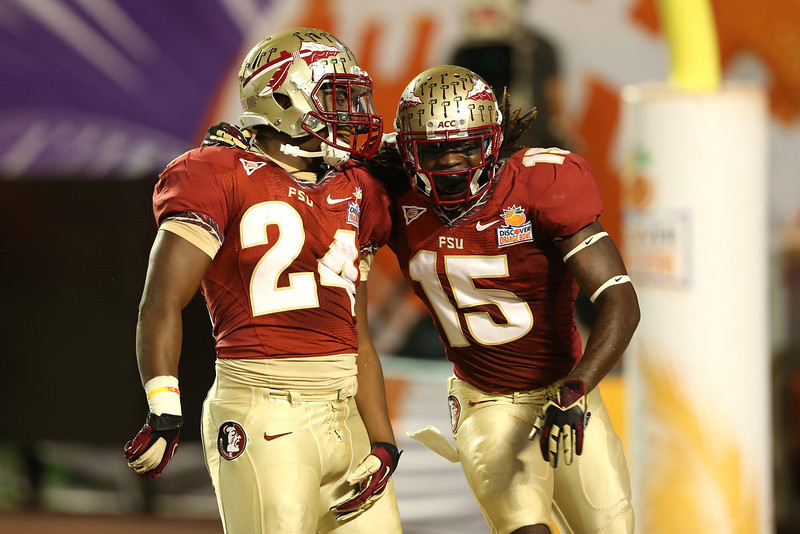 . (L-R) Lonnie Pryor #24 and Greg Dent #15 of the Florida State Seminoles celebrate after Pryor scored a 60-yard rushing touchdown in the first quarter against the Northern Illinois Huskies during the Discover Orange Bowl at Sun Life Stadium on January 1, 2013 in Miami Gardens, Florida.  (Photo by Streeter Lecka/Getty Images)