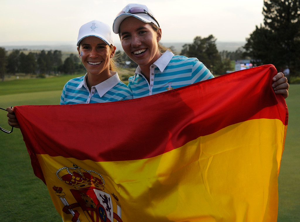 . PARKER, CO. - AUGUST 17: Spanish golfers Azahara Munoz, left, Carlota Ciganda, right, smiled with the Spanish flag on the 18th green after beating Americans Gerina Piller and Angela Stanford for a point Saturday at the Solheim Cup. It was the American Team versus the Europeans as play continued at the Colorado Golf Club Saturday afternoon, August 17, 2013. Photo By Karl Gehring/The Denver Post