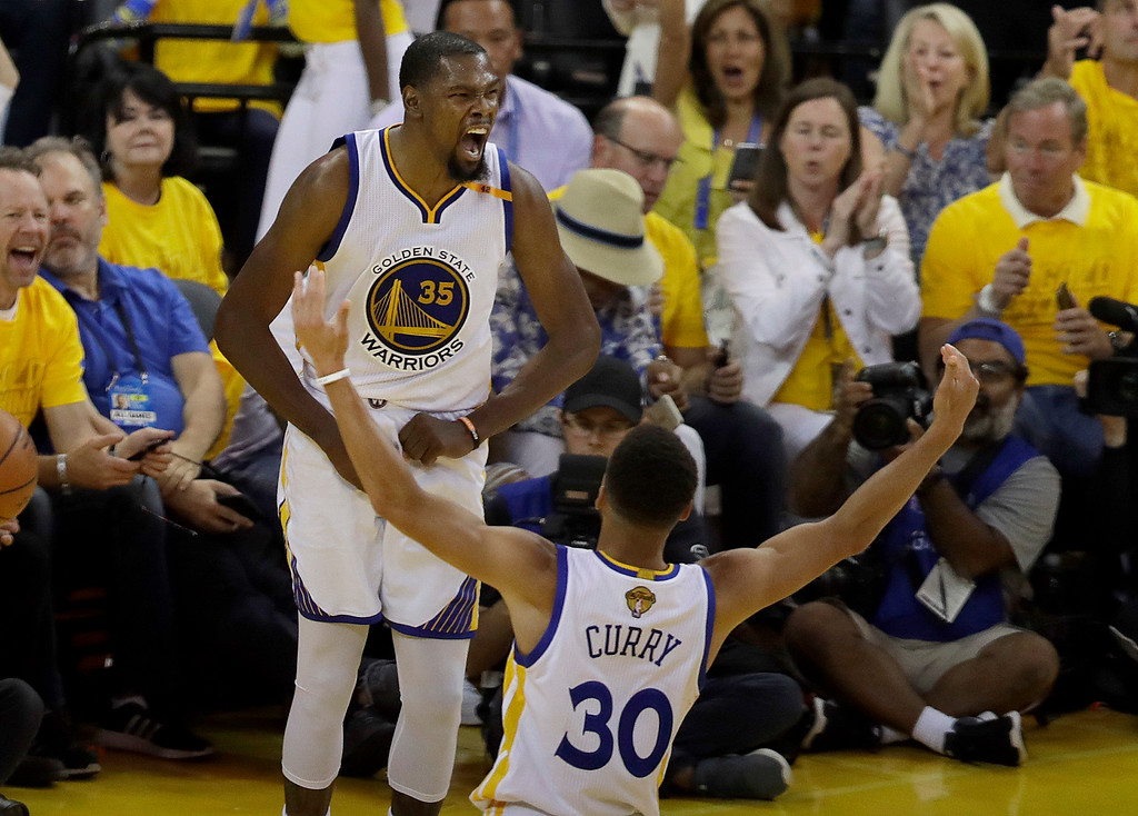 . Golden State Warriors forward Kevin Durant (35) celebrates with guard Stephen Curry (30) during the second half of Game 2 of basketball\'s NBA Finals against the Cleveland Cavaliers in Oakland, Calif., Sunday, June 4, 2017. (AP Photo/Marcio Jose Sanchez)