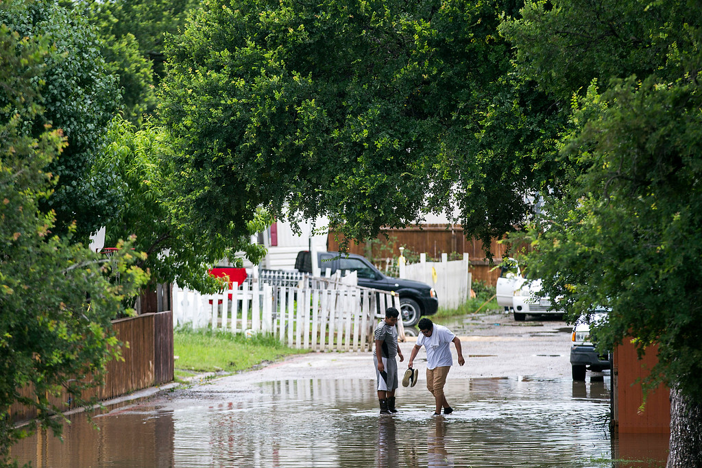 . Children wade through a flooded street as the waters from Mountain Creek rise in the Willow Bend mobile home park on Sunday, May 24, 2015, in Grand Prairie, Texas. The Dallas/Forth Worth received more than three inches of rain since midnight, with more reportedly on the way. (Smiley N. Pool/The Dallas Morning News via AP)