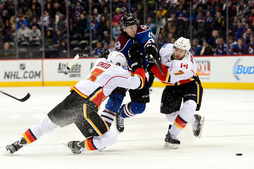. Nathan MacKinnon (29) of the Colorado Avalanche makes an athletic play to break through the defense of Ladislav Smid (3) of the Calgary Flames and T.J. Brodie (7) en route to narrowly missing a hat trick during the third period of the Flames\' 4-3 win.  (Photo by AAron Ontiveroz/The Denver Post)