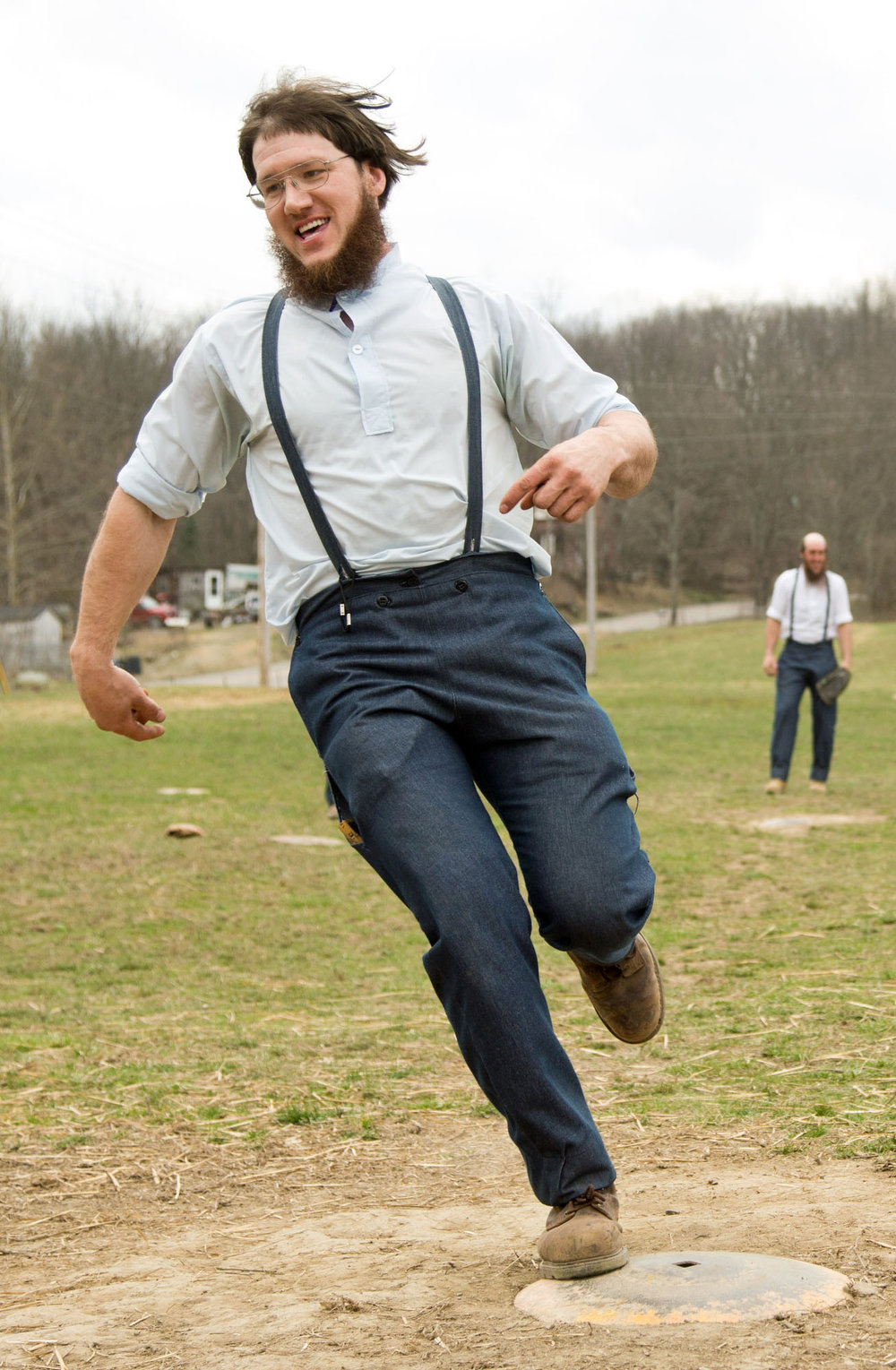 Description of . Freeman Burkholder crosses home plate during a game of baseball at the farewell picnic in Bergholz, Ohio on Tuesday, April 9, 2013.  Burkholder was sentenced to prison for his part in the hair and beard cutting scandal against other members of the Amish community. (AP Photo/Scott R. Galvin)
