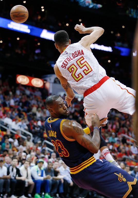 . Atlanta Hawks forward Thabo Sefolosha (25) falls into Cleveland Cavaliers forward LeBron James (23) in the first half of Game 3 of the second-round NBA basketball playoff series, Friday, May 6, 2016, in Atlanta. (AP Photo/John Bazemore)
