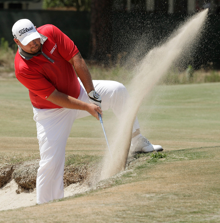. Brendon De Jonge, of Zimbabwe, hits out of the bunker on the third hole during the final round of the U.S. Open golf tournament in Pinehurst, N.C., Sunday, June 15, 2014. (AP Photo/Charlie Riedel)