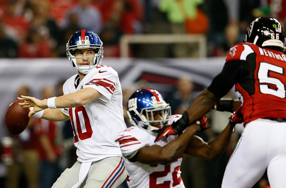 Description of . Eli Manning #10 of the New York Giants looks to pass against the Atlanta Falcons at Georgia Dome on December 16, 2012 in Atlanta, Georgia.  (Photo by Kevin C. Cox/Getty Images)