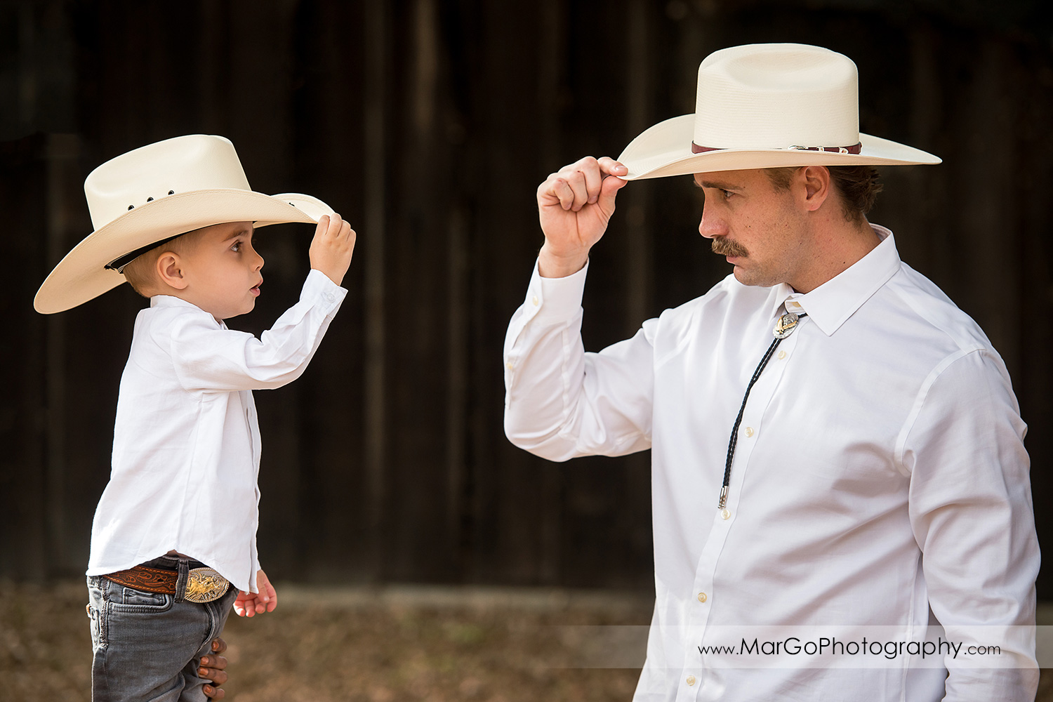 man and little boy in white shirts, gray jeans and cowboy hats looking at each other in Shinn Historical Park and Arboretum in Fremont