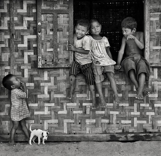 kids playing with their dog in a small village.  Myanmar, 2017