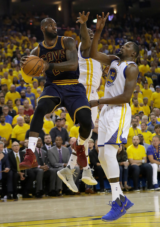 . Cleveland Cavaliers forward LeBron James, left, passes against Golden State Warriors forward Kevin Durant (35) and forward Draymond Green during the second half of Game 1 of basketball\'s NBA Finals in Oakland, Calif., Thursday, June 1, 2017. (AP Photo/Marcio Jose Sanchez)