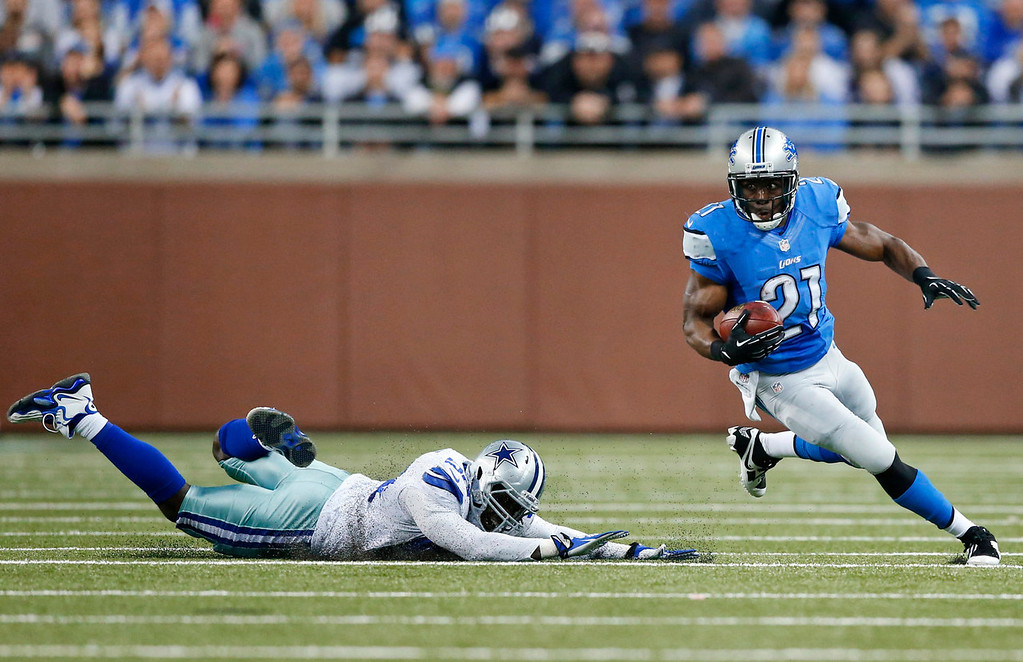 . Detroit Lions running back Reggie Bush (21) turns the corner on a diving Dallas Cowboys outside linebacker Justin Durant (52) in the second quarter of an NFL football game in Detroit, Sunday, Oct. 27, 2013. (AP Photo/Rick Osentoski)