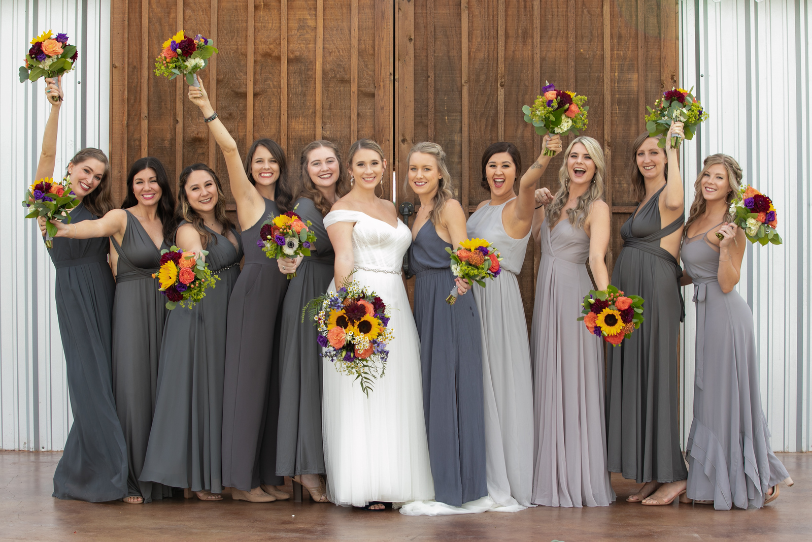 bride and 10 bridesmades smiling and raising their boquets standing in front of large wood doors at the entrance of the wedding venue
