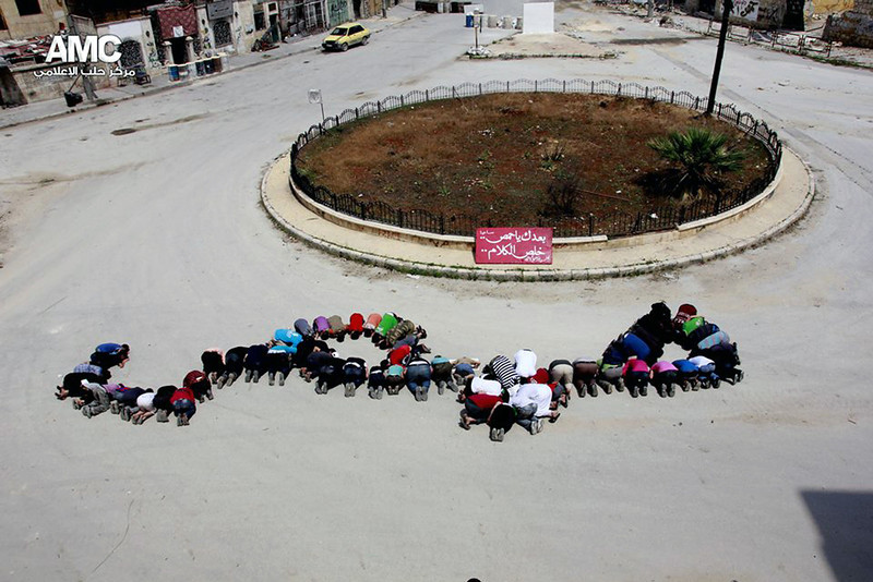 """. This photo provided by the anti-government activist group Aleppo Media Center (AMC), which has been authenticated based on its contents and other AP reporting, shows Syrian citizens forming the word Homs in Arabic with their bodies, in the Salaheddine district in Aleppo, Syria, Friday, May 9, 2014. Bulldozers cleared rubble Friday from the streets of battle-scarred districts in the central Syrian city of Homs after government troops entered the last rebel-held neighborhoods as part of an agreement that also granted opposition fighters safe exit from the city. The red placard with Arabic that reads,\""""no more words after Homs.\"""" (AP Photo/Aleppo Media Center AMC)"""