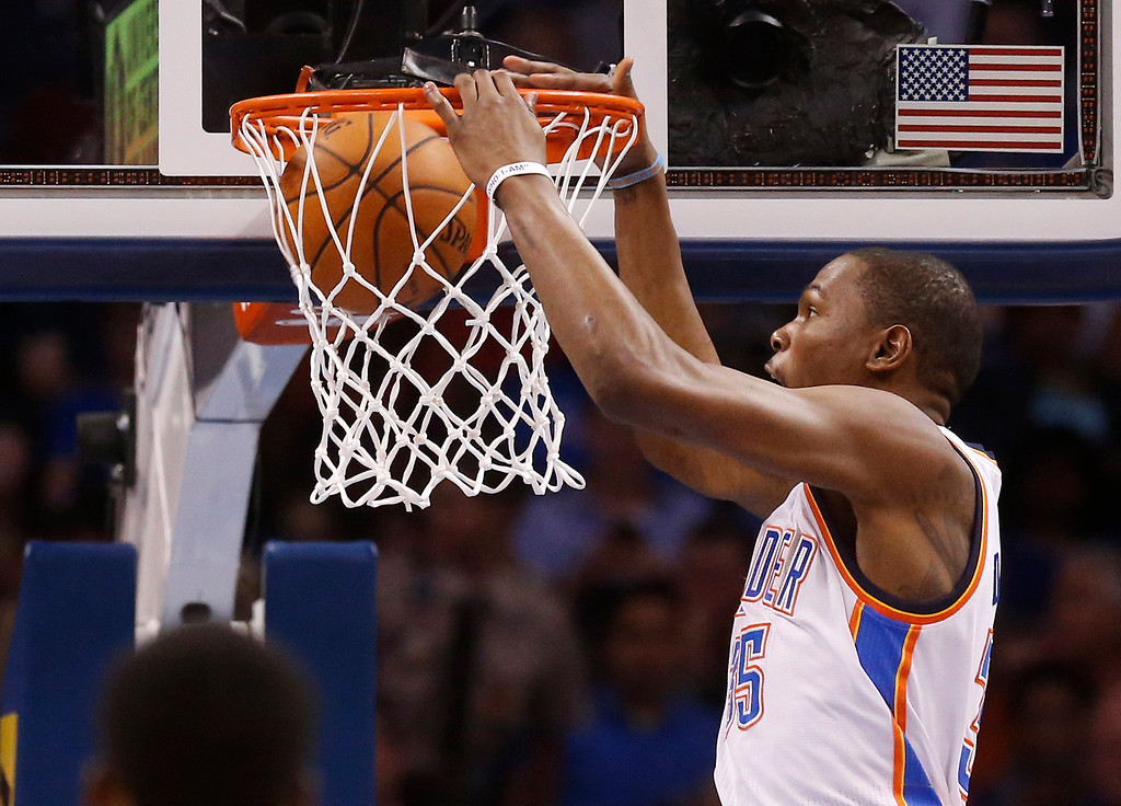 . Oklahoma City Thunder forward Kevin Durant (35) dunks in the second quarter of an NBA basketball game against the Denver Nuggets in Oklahoma City, Monday, March 24, 2014. (AP Photo/Sue Ogrocki)