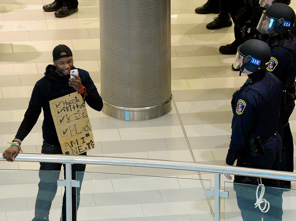 . A protester wears a sign as he talks on his phone. (Pioneer Press: John Autey)