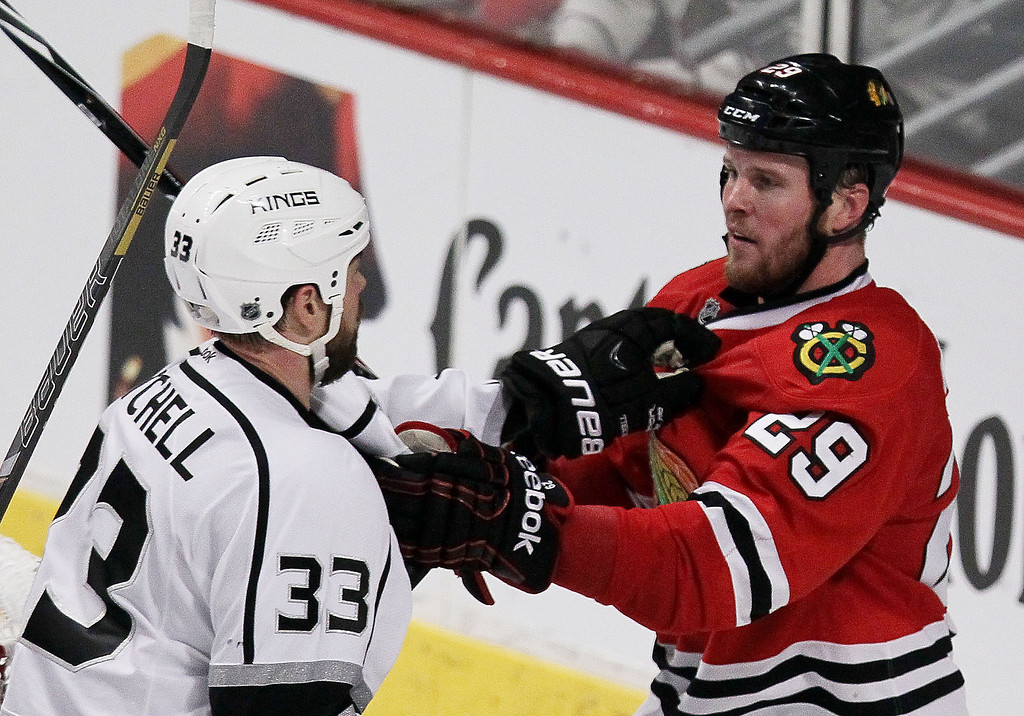 . Willie Mitchell #33 of the Los Angeles Kings and Bryan Bickell #29 of the Chicago Blackhawks fight in the third period in Game One of the Western Conference Final during the 2014 Stanley Cup Playoffs at United Center on May 18, 2014 in Chicago, Illinois.  (Photo by Tasos Katopodis/Getty Images)