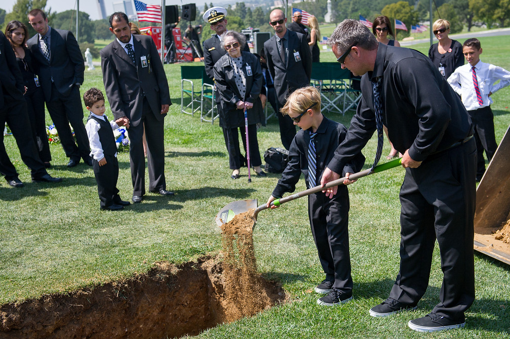 . Family members shovel dirt at the grave of LAPD officer Chris Cortijo, Tuesday, April 22, 2014, at Forest Lawn Hollywood Hills. (Photo by Michael Owen Baker/L.A. Daily News)