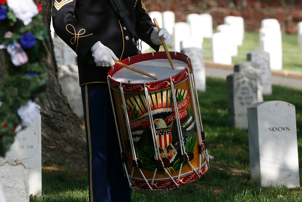 ". A U.S. Army honor guard band member plays a drum roll during the playing of ""Taps\"" at the gravesite of Army Pvt. William Christman, who was the first military burial at the cemetery, marking the beginning of commemorations of the 150th anniversary of Arlington National Cemetery in Arlington, Va., Tuesday, May 13, 2014.  (AP Photo)"