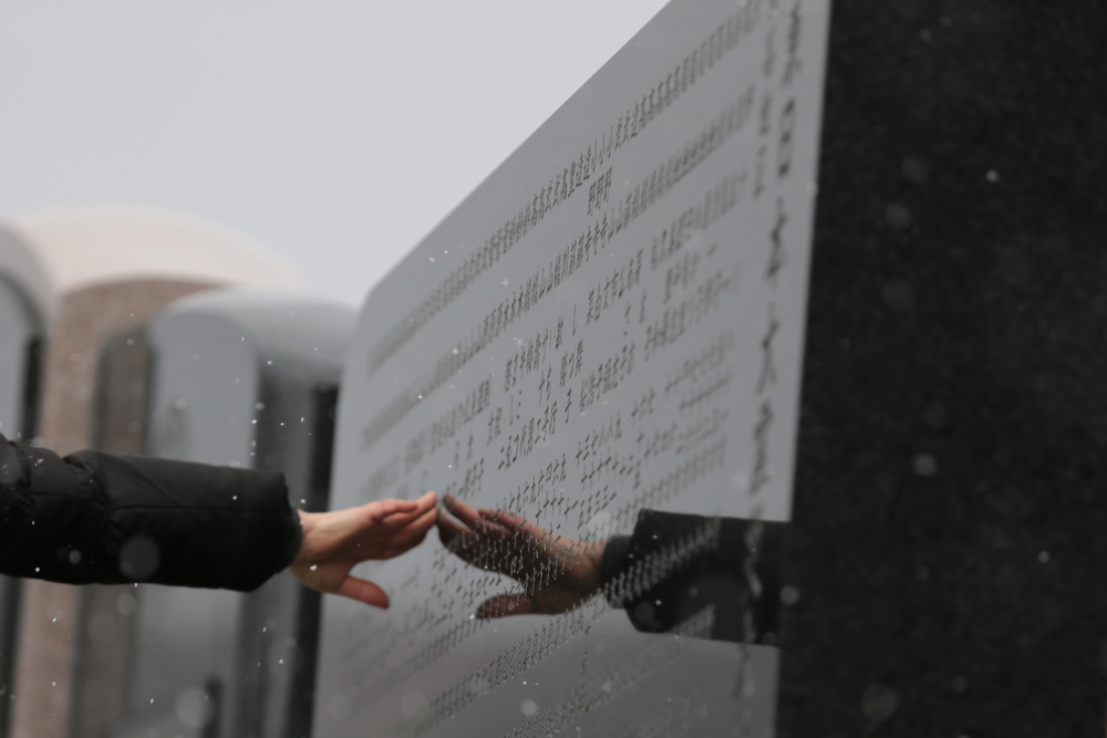 . A woman touches a memorial engraved with the names of the victims at Okawa Elementary School on the three year anniversary of the earthquake and tsunami on March 11, 2014 in Ishinomaki, Miyagi prefecture, Japan. On March 11 Japan commemorates the third anniversary of the magnitude 9.0 earthquake and tsunami that claimed more than 18,000 lives, and subsequent nuclear disaster at the Fukushima Daiichi Nuclear Power Plant.  (Photo by Yuriko Nakao/Getty Images)