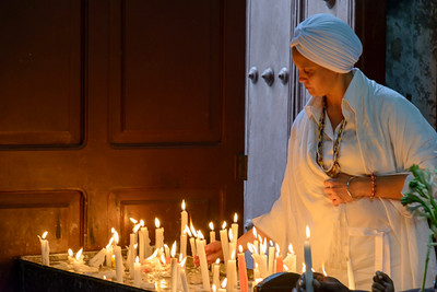 Woman in White Lighting Prayer Candles