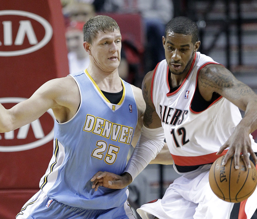 . Portland Trail Blazers forward LaMarcus Aldridge, right, works the ball in against Denver Nuggets center Timofey Mozgov, from Russia, during the first half of an NBA basketball game in Portland, Ore., Saturday, March 1, 2014. (AP Photo/Don Ryan)