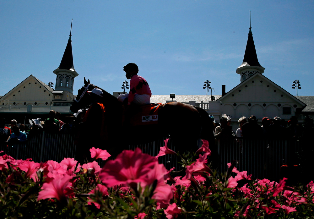 Description of . A horse and jockey walk past the twin spires prior to the 140th running of the Kentucky Derby at Churchill Downs on May 3, 2014 in Louisville, Kentucky.  (Photo by Kevin C. Cox/Getty Images)