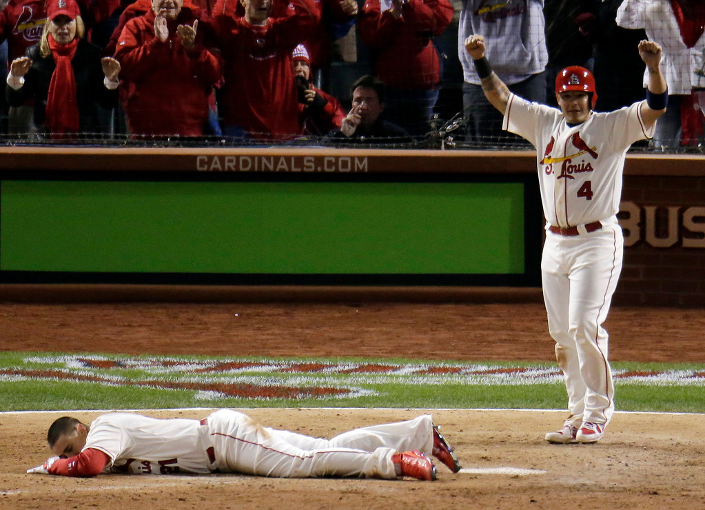 . St. Louis Cardinals\' Yadier Molina reacts as Allen Craig lays on home plate after getting tangled with Boston Red Sox\'s Will Middlebrooks during the ninth inning of Game 3 of baseball\'s World Series Saturday, Oct. 26, 2013, in St. Louis. Middlebrooks was called for obstruction on the play and Craig went in to score the game-winning run. The Cardinals won 5-4 to take a 2-1 lead in the series.(AP Photo/Charlie Riedel)