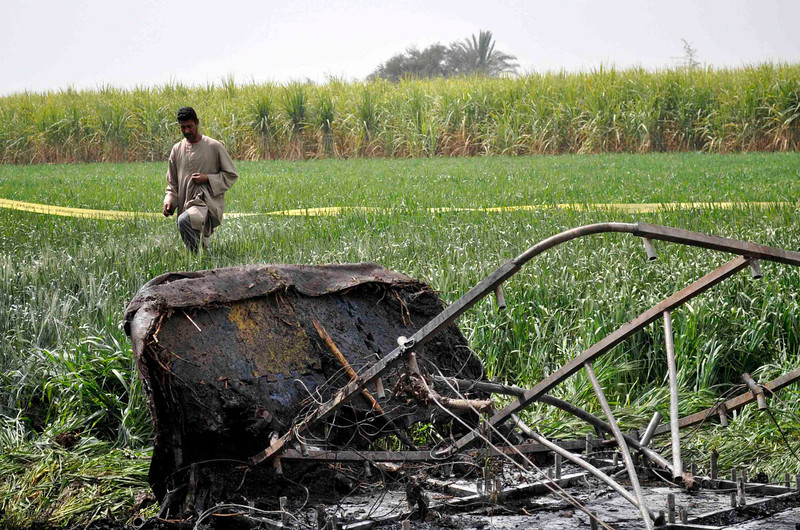 . A rescue official walks near the wreckage of a hot air balloon that crashed in Luxor February 26, 2013. A hot air balloon crashed near the Egyptian town of Luxor at dawn on Tuesday after a mid-air gas explosion, killing 19 Asian and European tourists, a local industry official and the state news agency said.  REUTERS/Stringer