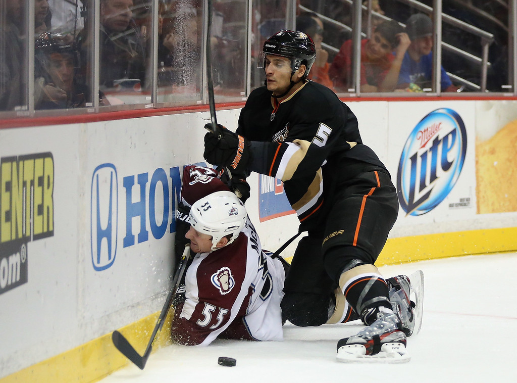 . Cody McLeod #55 of the Colorado Avalanche is checked into the boards by Luca Sbisa #5 of the Anaheim Ducks in the second period at Honda Center on February 24, 2013 in Anaheim, California.  (Photo by Jeff Gross/Getty Images)