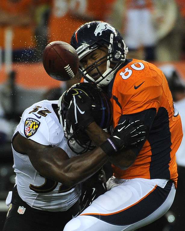 . DENVER, CO - SEPTEMBER 05: Denver Broncos tight end Julius Thomas (80) gets tackled by Baltimore Ravens strong safety James Ihedigbo (32) in the first quarter. The Denver Broncos took on the Baltimore Ravens in the first game of the 2013 season at Sports Authority Field at Mile High in Denver on September 5, 2013. (Photo by Tim Rasmussen/The Denver Post)